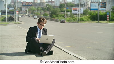 Urban business problems - Worried young businessman sitting...