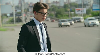 Waiting for a taxi - Young businessman standing near road...