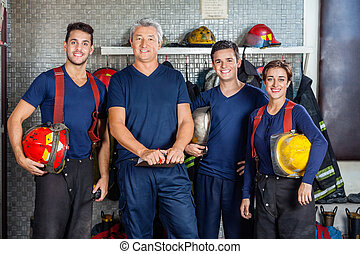 Confident Firefighters Standing At Fire Station - Portrait...