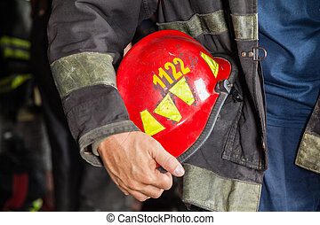 Firefighter Holding Red Helmet At Fire Station - Midsection...