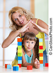 Mother forming house roof shape above child daughter -...