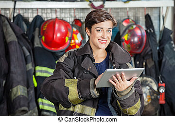Happy Firewoman Holding Digital Tablet At Fire Station -...