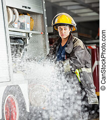 Confident Firewoman Spraying Water At Fire Station -...