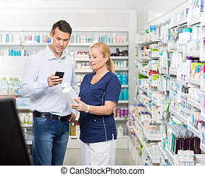 Customer Using Mobile Phone While Chemist Holding Products -...