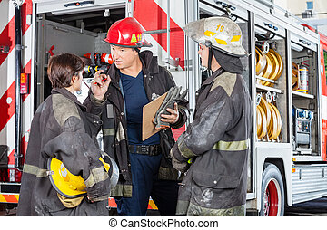 Firefighter Discussing With Colleagues Against Truck - Male...