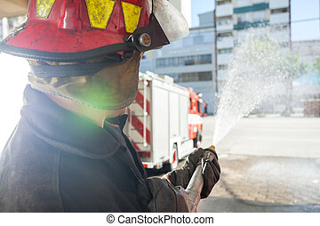 Firefighter Spraying Water While Practicing At Fire Station...