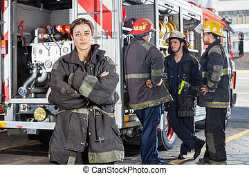 Confident Firewoman With Colleagues Standing By Truck -...