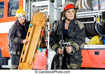 Confident Firefighter Holding Hose While Colleague Carrying...