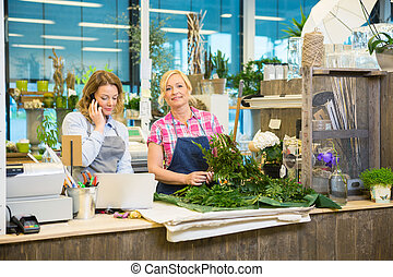 Florist Making Bouquet While Colleague Using Mobile Phone