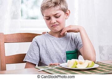 Boy refusing to eat apple - Blonde boy refusing to eat...