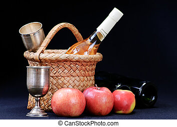 apples,wine glass and bottle in the basket on a black...