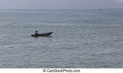 vietnamese fisherman drifts in boat rolling in sea waves -...
