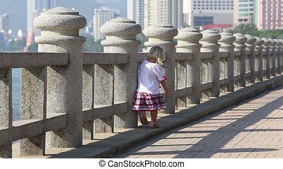 blonde girl in Ukrainian blouse runs by barrier on embankment