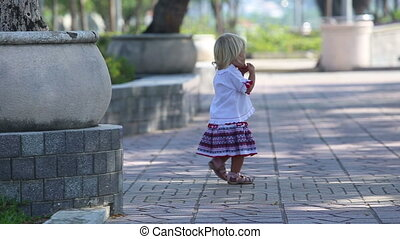 blonde girl in Ukrainian blouse comes to mother on embankment