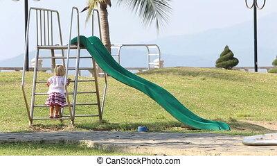 blonde girl in Ukrainian blouse climbs up on slide