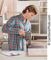 Carpenter Drilling Wood At Workshop