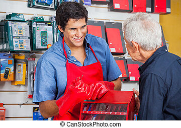 Salesman Showing Drill Bit To Man In Store - Smiling young...