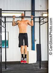 Male Athlete Doing Chin-Ups At Healthclub - Full length of...