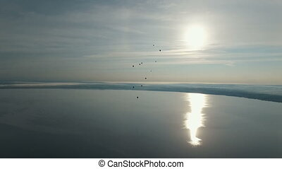 hot air baloons flying over the lake, aerial