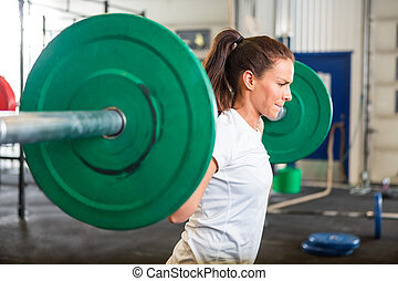 Fit Woman Lifting Barbell in Gym - Side view of fit young...