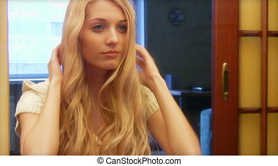 Beautiful young girl applying cosmetic in front of mirror -...