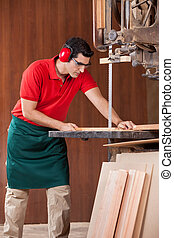 Carpenter Using Bandsaw To Cut Wooden Plank - Young male...