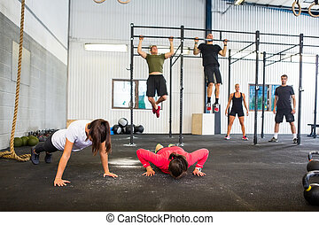 Athletes Exercising In Gym - Group of male and female...