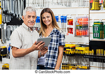 Woman And Father With Digital Tablet In Hardware Store -...