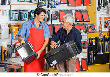 Man Looking At Salesman While Selecting Toolbox - Senior man...