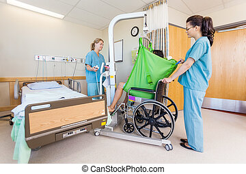 Female Nurses Transferring Patient From Hydraulic Lift To...