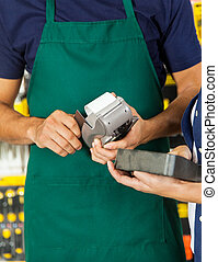 Worker Swiping Credit Card With Woman Holding Tool Set -...