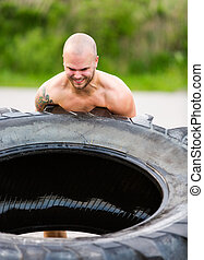 Determined Athlete Flipping Truck Tire - Determined male...