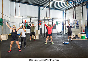 Instructor Assisting Athletes In Lifting Barbells - Crossfit...