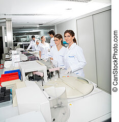 Technician And Colleague Working In Laboratory - Portrait of...