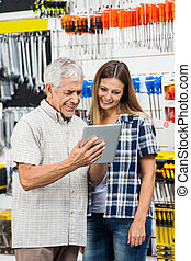 Family Using Tablet Computer In Hardware Shop - Happy father...