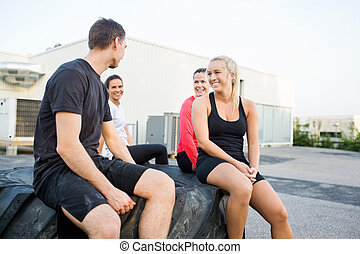 Friends Relaxing On Tire After Workout - Happy fit young...