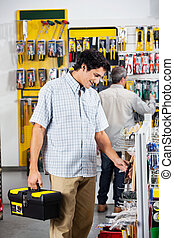 Customers Buying Tools In Store - Male customers buying...