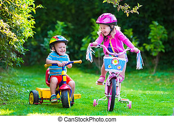 Two children riding bikes - Kids riding bikes in a park....