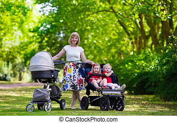 Woman with kids in stroller in a park - Young mother walking...