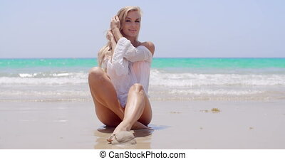 Seductive Young Woman Sitting on the Beach Sand - Seductive...