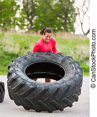 Athlete Flipping Truck Tire Outdoors - Young female athlete...