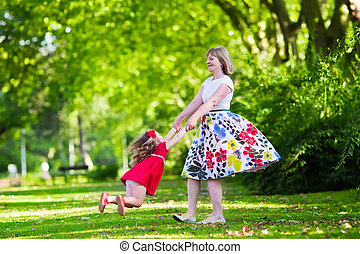 Young woman playing with little girl in a park