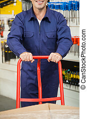 Worker Pushing Trolley In Hardware Store - Midsection of...