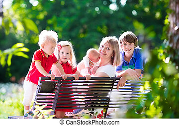 Family with kids relaxing on a park bench