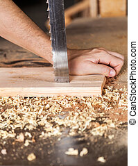 Carpenter's Hands Cutting Plank With Bandsaw - Closeup of...