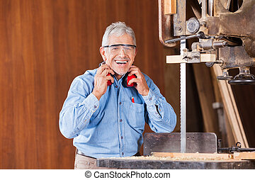 Happy Carpenter Holding Ear Protectors By Bandsaw - Portrait...