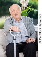 Portrait Of Happy Senior Man Holding Metal Cane - Portrait...