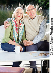 Senior Man Sitting With Arm Around Woman On Couch - Portrait...
