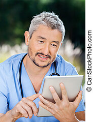 Male Nurse Using Tablet Computer - Male nurse using tablet...