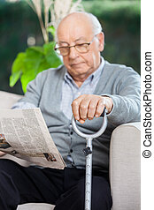 Elderly Man Reading Newspaper At Nursing Home Porch -...